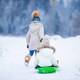 Little adorable girls enjoy a sleigh ride. Child sledding. Children play outdoors in snow. Family