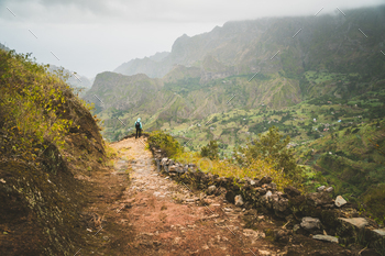 Man enjoying impressive mountainscape. Arid canyon valley extend far below. Santo Antao, Cabo Verde