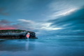 Long exposure of the sunset over the famous stone arch of As Catedrais beach - PhotoDune Item for Sale
