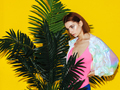 young modern female model near palm isolated on yellow background - PhotoDune Item for Sale