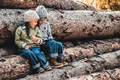 Children in the background of logs play with a smartphone. Watch the video and have fun. Friendship - PhotoDune Item for Sale