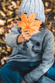 Little girl with autumn maple leaves. She covers her face with a leaf for fun - PhotoDune Item for Sale