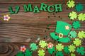 Happy Saint Patrick's mockup of handmade felt hat flowers and shamrock clover leaves on wooden table - PhotoDune Item for Sale
