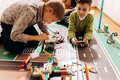 Two boys play with robots that they created from the robotic constructor on the colorful banner on - PhotoDune Item for Sale