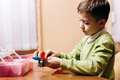 Boy dressed in green sweater sits at the table with opened box with details of robotic constructor - PhotoDune Item for Sale
