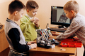 Three smart boys are making robots from the robotic constructor in the School of Robotics - PhotoDune Item for Sale