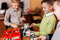 Three happy boys are making robots in the School of Robotics - PhotoDune Item for Sale