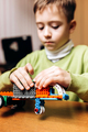 Focused boy dressed in green sweater sits at the table in the robotics school and makes a robot from - PhotoDune Item for Sale