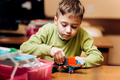 Boy dressed in green sweater sits at the table in the robotics school and makes a robot from the - PhotoDune Item for Sale