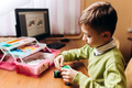Boy dressed in green sweater sits at the table with computer and robotic constructor and makes a - PhotoDune Item for Sale