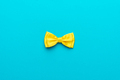 Minimalist Photo Of Yellow Bow Tie On Turquoise Blue Background And Copy Space - PhotoDune Item for Sale