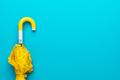 Folded Yellow Umbrella On Turquoise Blue Background - PhotoDune Item for Sale
