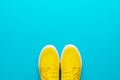 Pair Of Yellow Sneakers On Turquoise Blue Background With Copy Space - PhotoDune Item for Sale