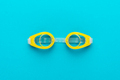 Yellow Swimming Goggles Over Blue Background With Central Composition - PhotoDune Item for Sale