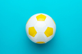 Close-Up Of White And Yellow Soccer Ball In Centre Of Turquoise Blue Background - PhotoDune Item for Sale
