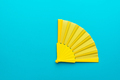 Minimalist Photo Of Yellow Hand Fan On Turquoise Blue Background With Copy Space - PhotoDune Item for Sale