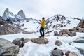 A hiker with a yellow jacket taking a photo on the base of Fitz Roy Mountain in Patagonia, Argentina - PhotoDune Item for Sale