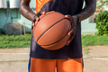 Young African American man holding a basket ball in an outdoors court, Cuba - PhotoDune Item for Sale