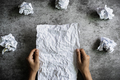 Hand holding crumpled paper on grunge background, Creativity problems concept - PhotoDune Item for Sale