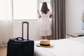 Young asian woman traveler with luggage standing at window in hotel room - PhotoDune Item for Sale