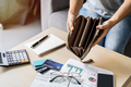 Stressed young woman open her empty wallet and calculating expenses at home - PhotoDune Item for Sale