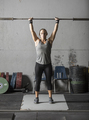Young woman warming up and getting ready for heavy lifting in gym. - PhotoDune Item for Sale