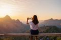 Young woman traveler taking photo with smart phone at sunset over the mountain - PhotoDune Item for Sale