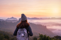 Young woman traveler looking at sea of mist and sunset over the mountain - PhotoDune Item for Sale