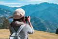 Young woman traveler taking a picture of beautiful landscape - PhotoDune Item for Sale