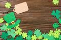 Happy Saint Patrick's mockup of handmade felt hat and shamrock clover leaves on wooden background. - PhotoDune Item for Sale