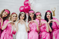 Lovely bridesmaids in pink robes and sleep masks with bride showing love sign with hands - PhotoDune Item for Sale