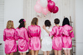 Bridesmaids in pink silk robes with the word 'bridesmaid' on bac - PhotoDune Item for Sale