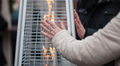 woman warmming hands in front of a gas heater - PhotoDune Item for Sale