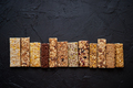 Various healthy granola bars placed in a row on black stone table - PhotoDune Item for Sale