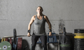 A strong young woman lifts a barbell in a gym, frontal view. - PhotoDune Item for Sale