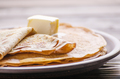Stack of French crepes with butter in ceramic dish on wooden kitchen table - PhotoDune Item for Sale