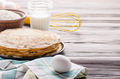 Stack of French crepes in frying pan on wooden kitchen table with milk eggs and flour aside - PhotoDune Item for Sale