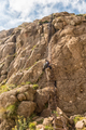 Hiker on the bottom chain ladders to top of Amphitheatre - PhotoDune Item for Sale