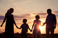 Happy family standing on the field at the sunset time. They build a house. - PhotoDune Item for Sale