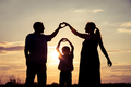 Happy family standing in the park at the sunset time. - PhotoDune Item for Sale