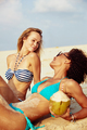 Two smiling female friends suntanning together on a tropical beach - PhotoDune Item for Sale