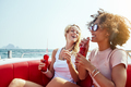 Two laughing young friends relaxing on a boat with drinks - PhotoDune Item for Sale