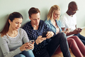 Businesspeople sitting on an office floor using their cellphones - PhotoDune Item for Sale