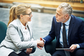 Mature business colleagues shaking hands together in an office lobby - PhotoDune Item for Sale