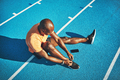 Young athlete tying up his shoes on a running track - PhotoDune Item for Sale
