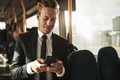 Smiling young businessman sending texts while riding on a bus - PhotoDune Item for Sale