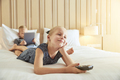 Smiling little girl watching television on a bed - PhotoDune Item for Sale