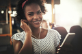 Smiling young African woman listening to music during her commute - PhotoDune Item for Sale