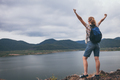 Happy woman standing near the lake at the day time. - PhotoDune Item for Sale