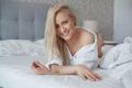 Beautiful middle aged woman lying on the bed, wearing white shirt and smiling - PhotoDune Item for Sale